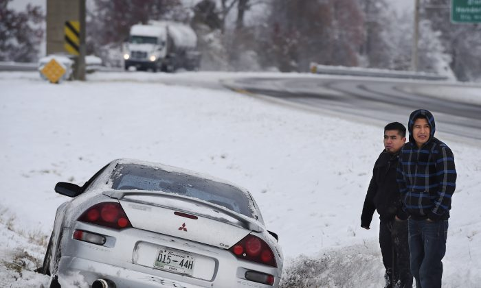 Stranded on the median, Angel Abendano, left, and Santiago Cuevas wait for assistance after losing control of their vehicle on the Pennyrile Parkway Monday, Nov. 17, 2014 after the first snow storm of the season dropped upwards of 5 inches of snow and ice on the area, closing schools. (AP Photo/The Gleaner, Mike Lawrence)