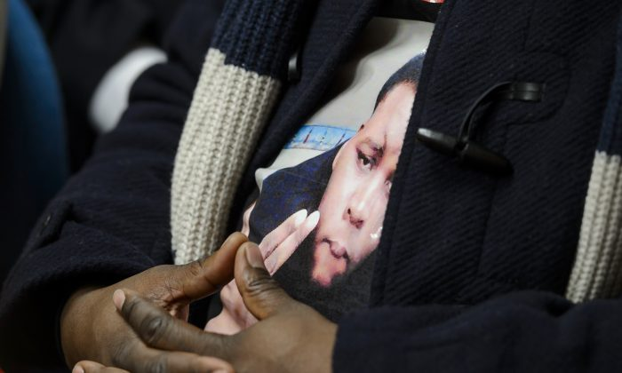 A portrait of Michael Brown, the unarmed black teenager who was shot and killed by a police officer in Ferguson, Missouri, last August, is worn by his father Michael Brown Sr. during a press conference on Nov. 12, 2014, in Geneva after a session of the United Nations Committee against Torture (CAT). The CAT committee members slammed police brutality that appears to disproportionately affect minorities. (Fabrice Coffrini/AFP/Getty Images)