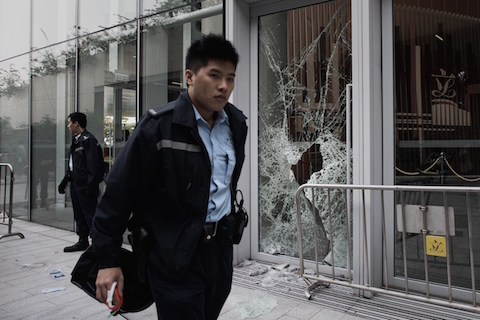 A policeman walks past a broken window of the government headquarters building in the Admiralty district of Hong Kong on November 19, 2014 after a small group attempted to break into the city's legislature. (Philippe Lopez/AFP/Getty Images)
