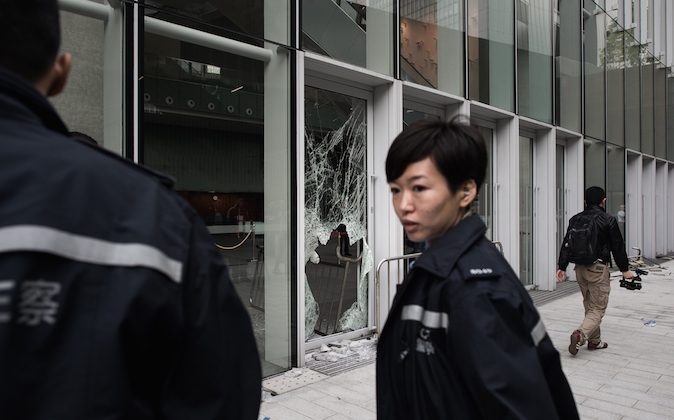 A policewoman stands by a broken window of the government headquarters building in the Admiralty district of Hong Kong on November 19, 2014. (Philippe LopezAFP/Getty Images)