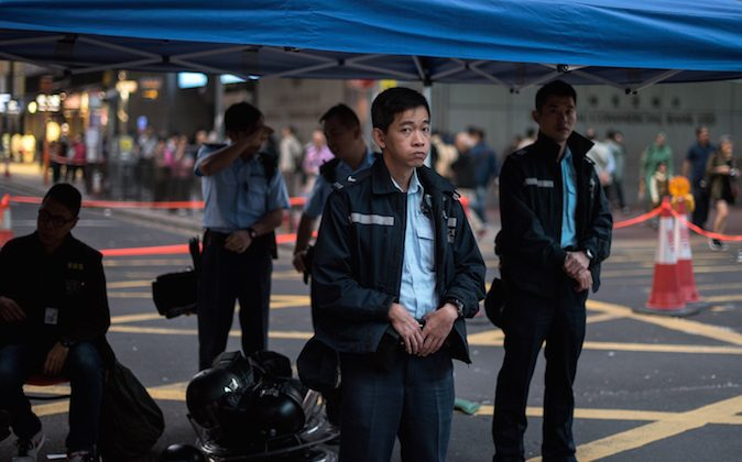 Hong Kong police officers look at a barricade built by pro-democracy protesters in the Mongkok district of Hong Kong on November 19, 2014. Hong Kong police clashed with pro-democracy demonstrators early on November 19 after a small group attempted to break into the city's legislature, with tensions spiking as court-ordered clearances of protest sites get under way.   (Alex Ogle/AFP/Getty Images)