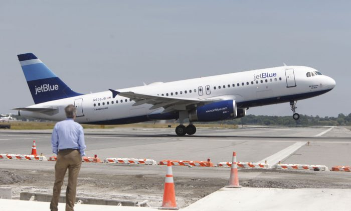 A man watches a JetBlue airplane take off from John F. Kennedy International Airport in New York on June 2, 2010. JetBlue Airways Corp. on Wednesday, Nov. 19, 2014, said that it will create three ticket classes, and only the top two include at least one free checked bag. The company didn't say what the bag fee would be for the cheapest flights. (AP Photo/Seth Wenig)