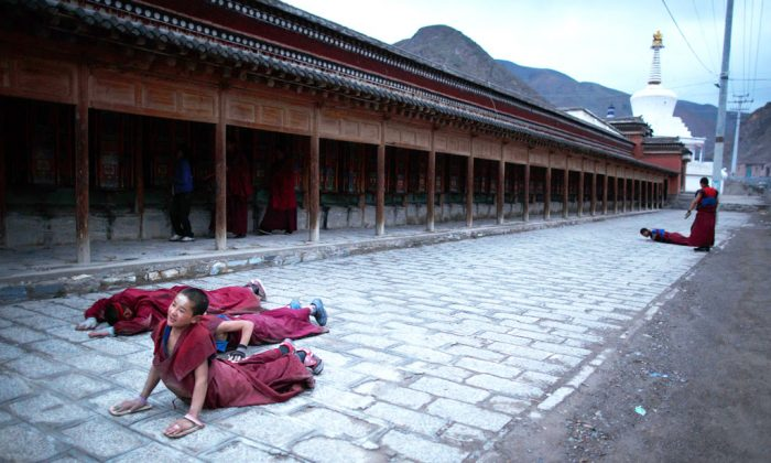 A young monk (L) prostrates near the Labrang monastery in Xiahe, Gansu province, a flashpoint for many Tibetan protests against Chinese authorities on May 16, 2013. More than 13o Tibetans have set themselves alight since 2009, with most dying of their injuries, in demonstrations against what they view as Chinese oppression. Beijing rejects such claims, pointing to substantial investment in Tibet and other regions with large Tibetan populations, although critics say economic development has brought an influx of ethnic Han Chinese and eroded traditional Tibetan culture. (Ed Jones/AFP/Getty Images)