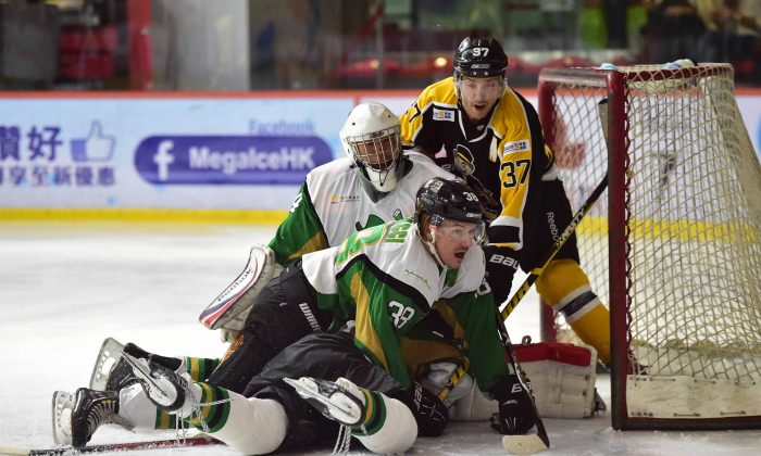 Jeff Ceccacci of Macau Aces helps goalie Emerson Keung to ward off an attack by Kory Falite of Hong Kong Tycoons in their CIHL match at Mega Ice on Saturday Nov 15, 2014. (Bill Cox/Epoch Times)