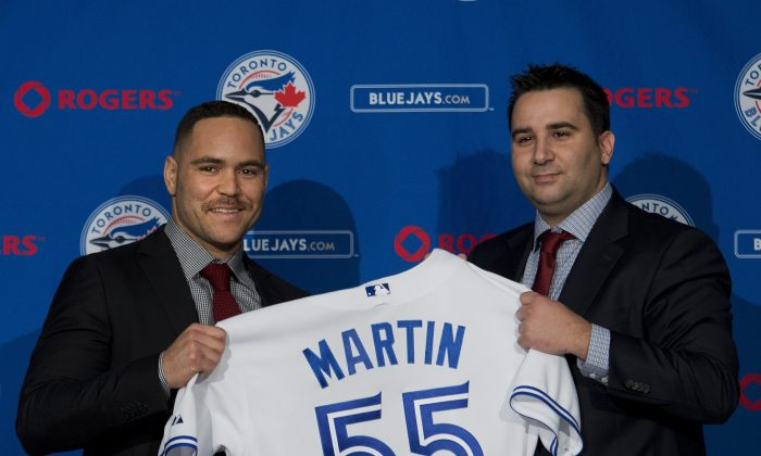 Toronto Blues Jays newly-signed catcher Russell Martin, left, and general manager Alex Anthopoulos hold up a jersey during a baseball press conference in Toronto, Thursday, Nov. 20, 2014. (AP Photo/The Canadian Press, Nathan Denette)