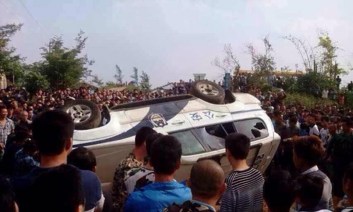 Protesters stand around an upside down police vehicle in Haikou, Hainan Province, China, on Nov. 18. A mass protest against construction of a prevention center in Haikou, Hainan Province turned into a clash with police shooting rubber bullets and protesters smashing the police vehicles, on Nov. 18, 2014. (Internet photo)