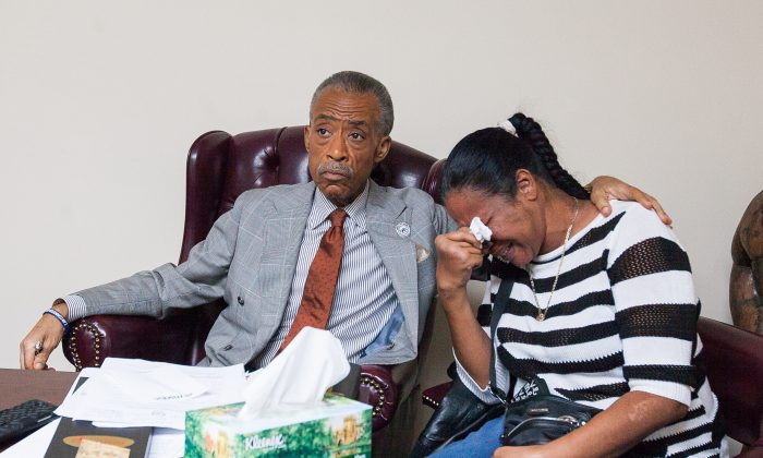 Rev. Al Sharpton comforts Esaw Garner while watching a broadcast of a decision of St. Louis Grand Jury to not indict police officer Darren Wilson for killing Michael Brown. National Action Network office in Harlem, New York, on Nov. 24, 2014. (Petr Svab/Epoch Times)