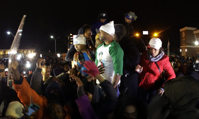 Lesley McSpadden, the mother of Michael Brown, left standing on the top of a car, reacts as she listens to the announcement of the grand jury decision Monday, Nov. 24, 2014, in Ferguson, Mo. A grand jury has decided not to indict Ferguson police officer Darren Wilson in the death of Michael Brown, the unarmed, black 18-year-old whose fatal shooting sparked sometimes violent protests. (AP Photo/Charlie Riedel)