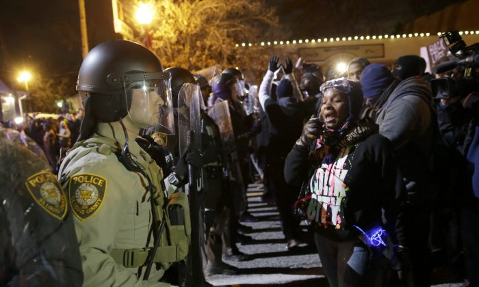 Police officers and protesters ready to react to the announcement of the grand jury decision not to indict police officer Darren Wilson in the fatal shooting of Michael Brown, an unarmed black 18-year-old, in Ferguson, Mo., on Nov. 24, 2014. (AP Photo/David Goldman)