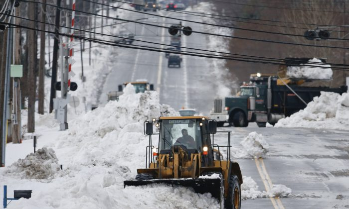 A front loader clears snow from Lake Avenue on Sunday, Nov. 23, 2014, in Orchard Park, N.Y. Western New York continues to dig out from the heavy snow dropped this week by lake-effect snowstorms. (AP Photo/Mike Groll)