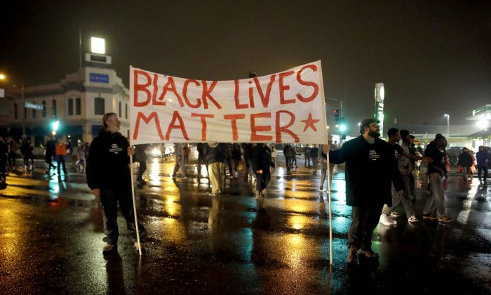 Protesters stand in the middle of a busy intersection blocking traffic Sunday, Nov. 23, 2014, in St. Louis. Ferguson and the St. Louis region are on edge in anticipation of the announcement by a grand jury whether to criminally charge officer Darren Wilson in the killing of 18-year-old Michael Brown. (AP Photo/Jeff Roberson)