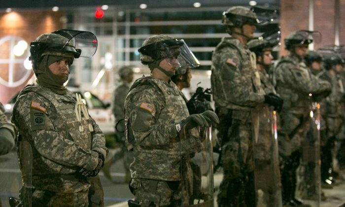 The National Guard stands by after protesters set fires and fired gun shots the night before in Ferguson, Mo., on Tuesday, Nov. 25, 2014. (Benjamin Chasteen/Epoch Times)