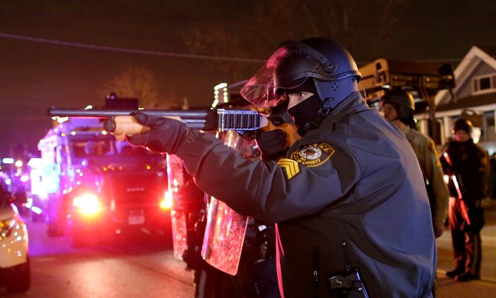 A police officer points a shotgun at protestors during a demonstration on November 24, 2014 in Ferguson, Missouri. A St. Louis County grand jury has decided to not indict Ferguson police Officer Darren Wilson in the shooting of Michael Brown that sparked riots in Ferguson, Missouri in August. (Photo by Justin Sullivan/Getty Images)
