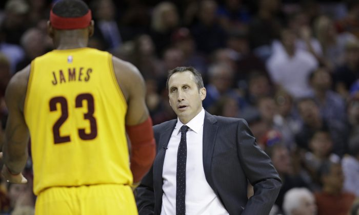 Cleveland Cavaliers head coach David Blatt, right, talks with Cleveland Cavaliers' LeBron James during an NBA basketball game against the San Antonio Spurs Wednesday, Nov. 19, 2014, in Cleveland. (AP Photo/Tony Dejak)