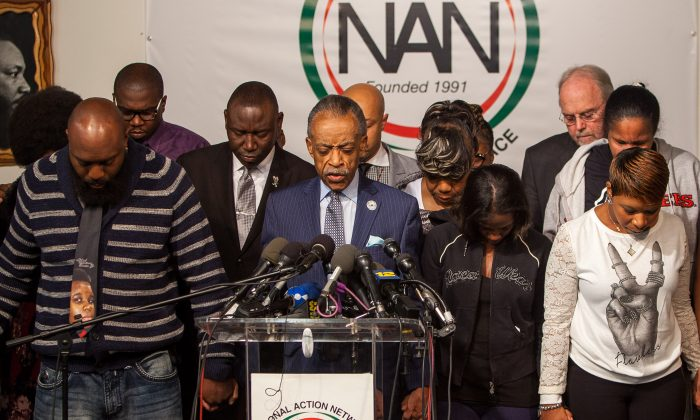 Rev. Al Sharpton leads a prayer with the family members of Michael Brown, Eric Garner, and Akai Gurley, black men who died during encounters with police, in Harlem, on Nov. 26, 2014. (Petr Svab/Epoch Times)