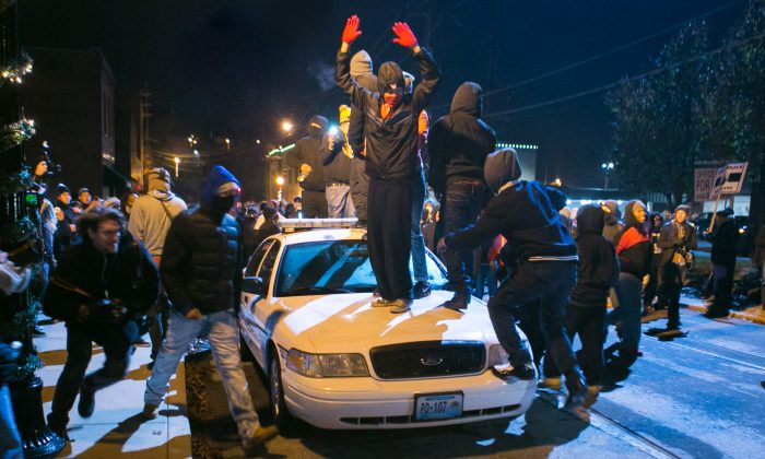 Activists stand and jump on a police car before hurling rocks and lighting it on fire in Ferguson, Mo., on Nov. 25, 2014. (Benjamin Chasteen/Epoch Times)