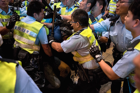 Police officers surround a pro-democracy protester (C) and restrain him in the Mongkok district of Hong Kong on November 26, 2014. (Alex Ogle/AFP/Getty Images)