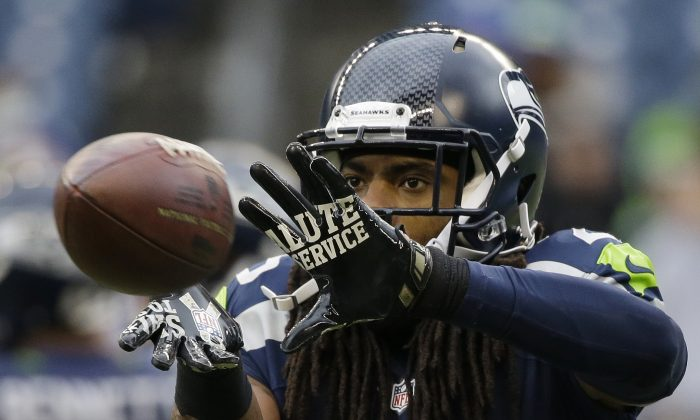 """FILE - In this Nov. 9, 2014,  file photo, Seattle Seahawks cornerback Richard Sherman warms ups before an NFL football game against the New York Giants in Seattle. For the first time since flexible scheduling came to """"Sunday Night Football"""" in 2006, the NFL could go an entire season without needing it. Seahawks-Cardinals in Week 16 keeps getting juicer with Arizona's improbable run to the league's best record and the defending Super Bowl champs' wobbly playoff hopes. (AP Photo/Elaine Thompson, File)"""