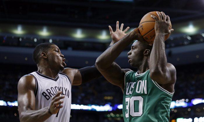 Boston Celtics forward Brandon Bass (30) prepares to shoot against Brooklyn Nets guard Joe Johnson (7) in the first quarter of an NBA basketball game in Boston, Wednesday, Oct. 29, 2014. (AP Photo/Elise Amendola)