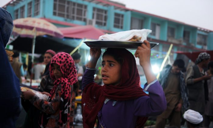 An Afghan girl sells a typical Afghan flat bread in the streets of Mazar-i-Sharif on July 1, 2014. (Farshad Usyan/AFP/Getty Images)