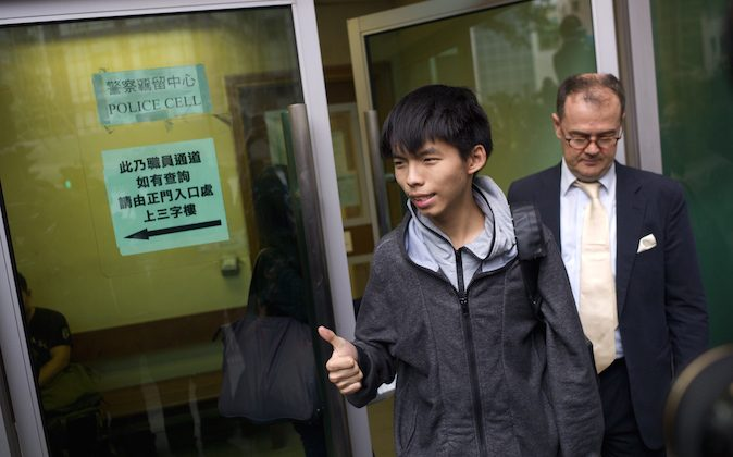 Student leader Joshua Wong (C) gives a thumbs up as he exits a courthouse with his lawyer Michael Vidler after Wong was released on bail in Hong Kong on November 27, 2014. (Aaron Tam/AFP/Getty Images)