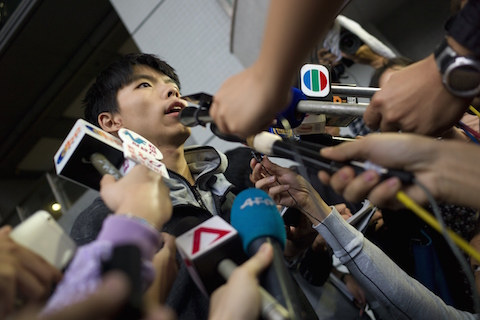 Student leader Joshua Wong (L) speaks to reporters outside a courthouse after he was released on bail in Hong Kong on November 27, 2014. A court in the semi-autonomous city banned the pro-democracy leader from entering a busy urban district one day after he was arrested from a major protest site when police moved in to clear out protesters. (Aaron Tam/AFP/Getty Images)