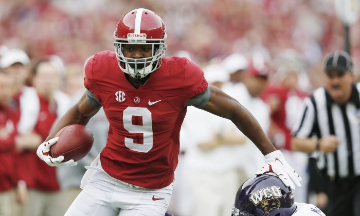 Alabama wide receiver Amari Cooper (9) avoids the tackle from Western Carolina defensive back A.J. McKoy (30) during the first half of an NCAA college football game, Saturday, Nov. 22, 2014, in Tuscaloosa, Ala. Cooper limped off the field after an injury on the play. (AP Photo/Brynn Anderson)