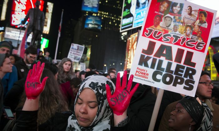 In this Nov. 25, 2014 file photo, demonstrator Maryam Said raises her painted hands during a protest against a grand jury's decision on Monday not to indict Ferguson police officer Darren Wilson in the shooting of Michael Brown in New York. (AP Photo/John Minchillo, File)