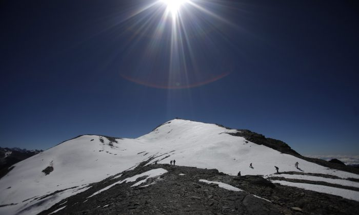 In this June 12, 2011 file photo, people walk along the Cordillera Real of the Andes mountains on the outskirts of La Paz, Bolivia. According to the Environmental Defense League, a Bolivian NGO, Bolivia's glaciers along the Cordillera Real, Chacaltaya, Tuni Condorini and Illimani are shrinking in size by more than one meter every year and estimate that the majority of the snow in this area could disappear by 2030. A scientific assessment by the U.N.'s expert panel on climate change warned that rising global temperatures could have an irreversible impact on people and ecosystems as glaciers melt, sea levels rise, heat waves intensify and oceans become warmer and more acidic. (AP Photo/Juan Karita)