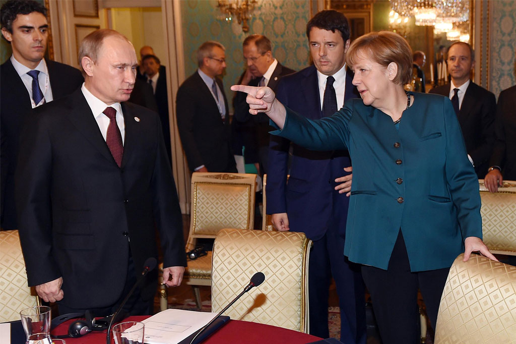 German Chancellor Angela Merkel (R) speaks to Russia's President Vladimir Putin (L) as Italian Prime Minister Matteo Renzi looks on prior to their meeting on Ukraine's crisis with Ukrainian President Petro Poroshenko (not seen), on the sidelines of the 10th Asia–Europe Meeting (ASEM) summit in Milan on Oct. 17, 2014. (Daniel dal Zennaro/AFP/Getty Images)