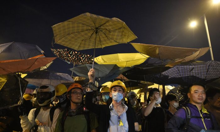 Demonstrators hold umbrellas, a symbol of the pro-democracy protests, amid a clash with police during the protest near the government headquarters in Hong Kong on Nov. 30, 2014. Protesters want free elections in 2017 for Hong Kong's leader, whom Beijing says must be vetted through a loyalist committee. (Philippe Lopez/AFP/Getty Images)