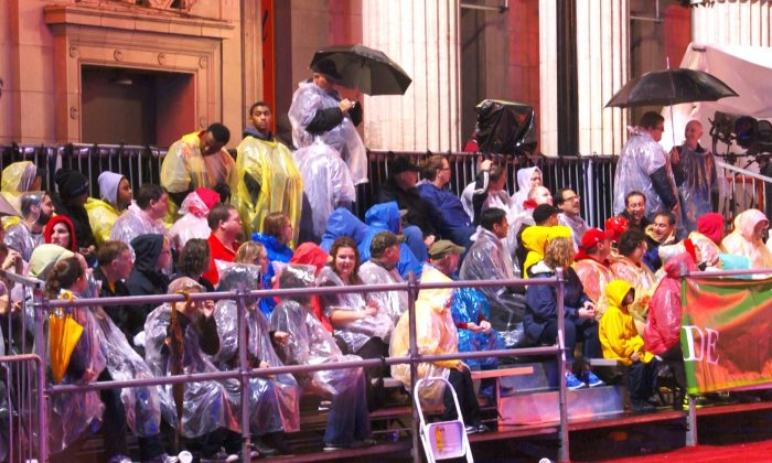 Spectators watch the Hollywood Christmas Parade in Los Angeles on Nov. 30, 2014. A rainstorm drenched the event, causing many parade-goers to seek out ponchos and umbrellas. (Yang Yang/Epoch Times)