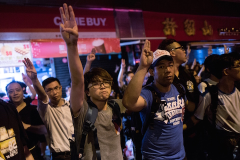"Pro-democracy protesters  flash the three-finger salute from the ""The Hunger Games"" in the Mongkok district of Hong Kong on November 29, 2014. (Alex Ogle/AFP/Getty Images)"