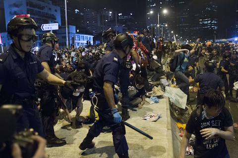 Police charge towards pro-democracy protesters near the government headquarters in the Admiralty district of Hong Kong early on December 1, 2014. (Dale de la Rey/AFP/Getty Images)