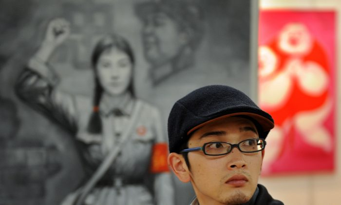 A Chinese man walks past a painting of a Red Guard from China's Cultural Revolution period at an art exhibit in Shanghai on April 17, 2008. (Mark Ralston/AFP/Getty Images)