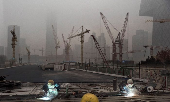 Chinese workers weld at a construction site in heavy pollution on Nov. 29, 2014, in Beijing, China. (Kevin Frayer/Getty Images)