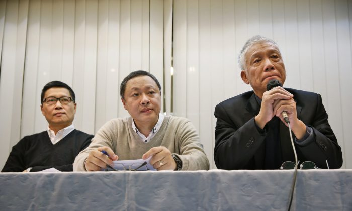 Three protest leaders, from left, Chan Kin-man, Benny Tai Yiu-ting and Chu Yiu-ming, attend a news conference in Hong Kong Tuesday, Dec. 2, 2014 as they announce that they will surrender to police. (AP Photo/Kin Cheung)