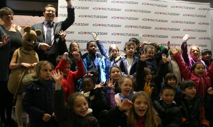 Children cheer in the lobby of 92nd Street Y, a community center on the Upper East Side, Manhattan, N.Y., on Dec. 2, 2014, after attending a musical concert in support of Giving Tuesday. (Shannon Liao/Epoch Times)