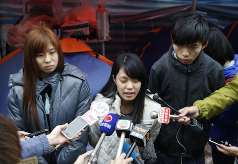 Three students, from right, Joshua Wong, Prince Wong and Isabella Lo speak to the media during their hunger strike at the occupied area outside government headquarters in Hong Kong Tuesday, Dec. 2, 2014. (AP Photo/Kin Cheung)