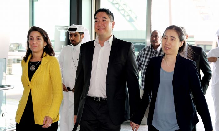 American couple Grace, right, and Matthew Huang walk to their departure gate with U.S. Ambassador to Qatar, Dana Shell Smith, left, at the Hamad International Airport in Doha, Qatar, on Nov. 30, 2014. After nearly two years of detention in the Gulf country, the couple were relieved of all charges but were prevented from leaving the country. (Osama Faisal/AP Photo)