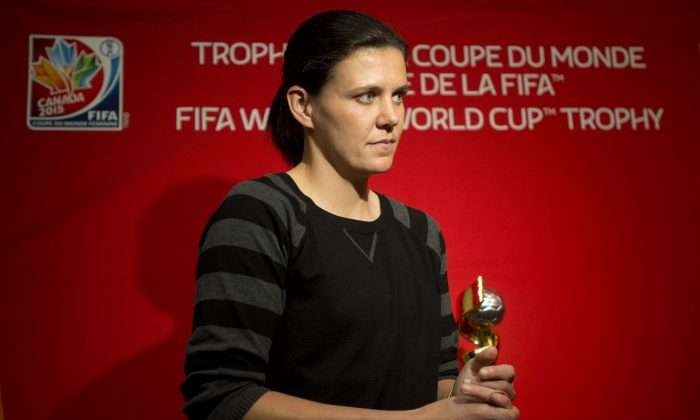 Canadian women's national soccer team captain Christine Sinclair stands near the Women's World Cup trophy following a news conference Friday, Dec. 5, 2014 in Ottawa. (The Canadian Press/Adrian Wyld)