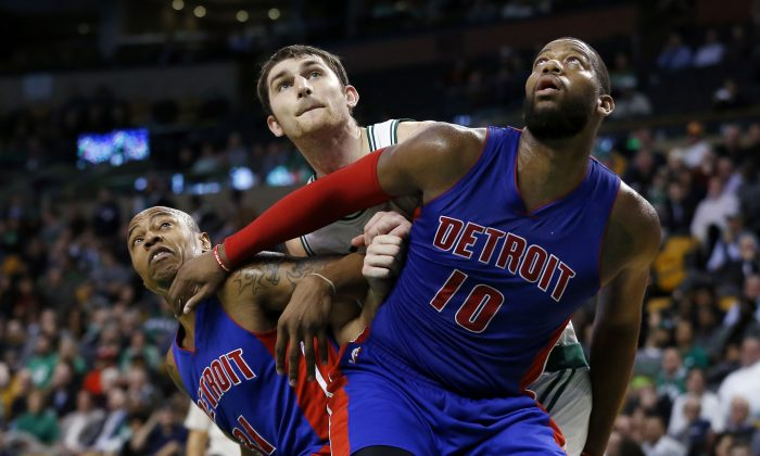 Detroit Pistons forward Caron Butler (31) and forward Greg Monroe (10) box out Boston Celtics center Tyler Zeller during the second half of an NBA basketball game in Boston, Wednesday, Dec. 3, 2014. (AP Photo/Elise Amendola)