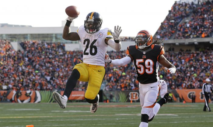 Pittsburgh Steelers running back Le'Veon Bell (26) scores on a 10-yard touchdown reception against Cincinnati Bengals outside linebacker Emmanuel Lamur (59) during the second half of an NFL football game Sunday, Dec. 7, 2014 in Cincinnati. (AP Photo/Michael Conroy)