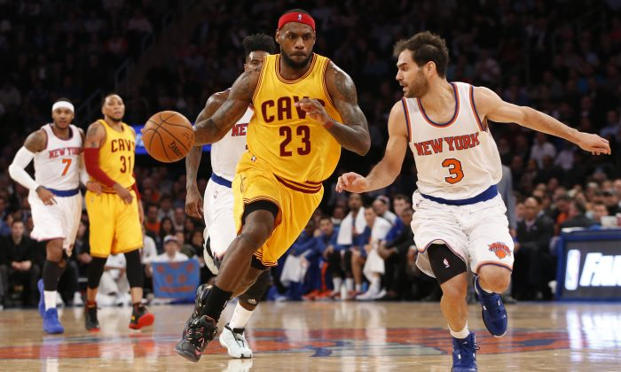 Cleveland Cavaliers forward LeBron James (23) drives toward the basket beside New York Knicks guard Jose Calderon (3) in the first half of an NBA basketball game at Madison Square Garden in New York, Thursday, Dec. 4, 2014. (AP Photo/Kathy Willens)