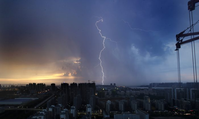 Lightning strikes at sunset in Wuhan, the capital of central China's Hubei Province, on Aug. 11, 2013. Real estate business has become an important part of Xi Jinping's anti-corruption campaign against the Jiang faction. (STR/AFP/Getty Images)