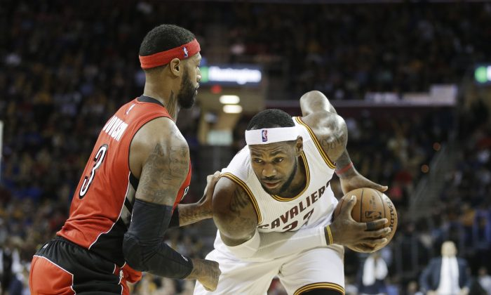 Cleveland Cavaliers' LeBron James, right, goes against Toronto Raptors' James Johnson (3) in the fourth quarter of an NBA basketball game Tuesday, Dec. 9, 2014, in Cleveland. (AP Photo/Mark Duncan)