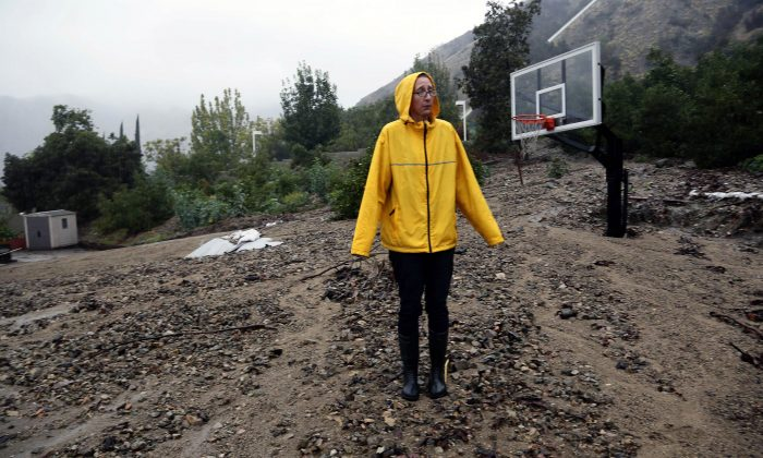 Homeowner Amanda Heinlein stands on a mud landslide covering a basketball court near her house in Azusa, Calif., Friday, Dec. 12, 2014.   A soaking storm swept into  California, causing several mudslides, flooding streets and cutting power to tens of thousands Friday after lashing the rest of the state with much-needed rain.   (AP Photo/Nick Ut)