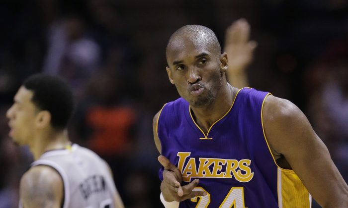 Los Angeles Lakers' Kobe Bryant (24) celebrates after he scored against the San Antonio Spurs during the second half of an NBA basketball game, Friday, Dec. 12, 2014, in San Antonio.  Los Angeles won 112-110. (AP Photo/Eric Gay)