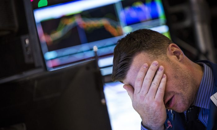 A trader reacts on the floor of the New York Stock Exchanged after the Dow Jones Industrial Average took plunged over 250 points on Dec. 10, 2014. (Andrew Burton/Getty Images)