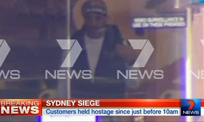 This image taken from video shows a man believed to be a gunman inside a cafe in Sydney, Australia Monday, Dec. 15, 2014. An apparent hostage situation was unfolding inside the chocolate shop and cafe in Australia's largest city on Monday, where several people could be seen through a window with their hands held in the air. (AP Photo/Channel 7 via AP Video)